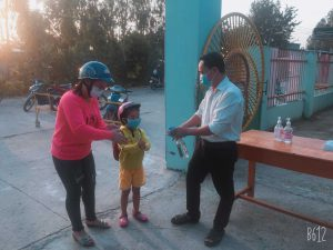 Phụ huynh đưa trẻ vào trường, trẻ được đo thân nhiệt và rửa tay